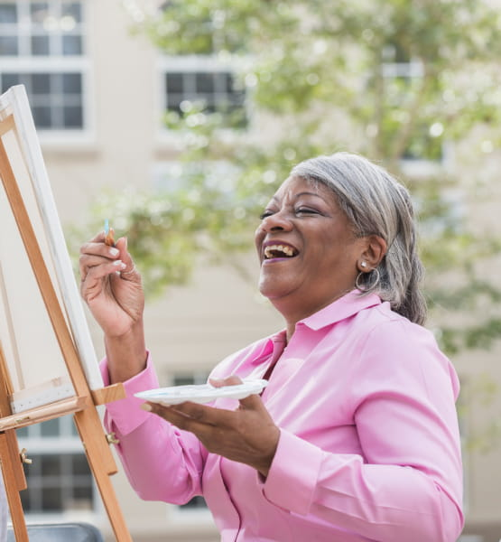 woman laughing while painting
